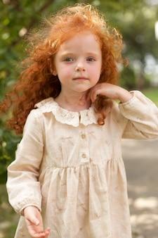 夕暮れ時の野原で野の花の中でポーズをとる紫色のドレスを着た赤い巻き毛の美しい少女。肖像画。
