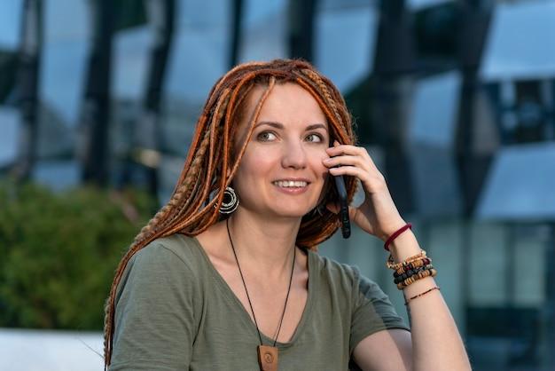 빨간 향취를 가진 아름다운 소녀는 전화로 친구들과 즐겁게 소통합니다. 여름 거리에 웃는 소녀