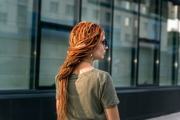 Красивая девушка с красными дредами позирует на фоне офисного здания. уличное фото