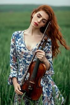赤い髪と花の自然分野でバイオリンを保持している青いドレスの美しい少女。