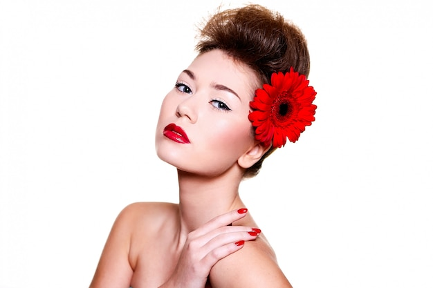 Beautiful girl with red lips flower on her hair