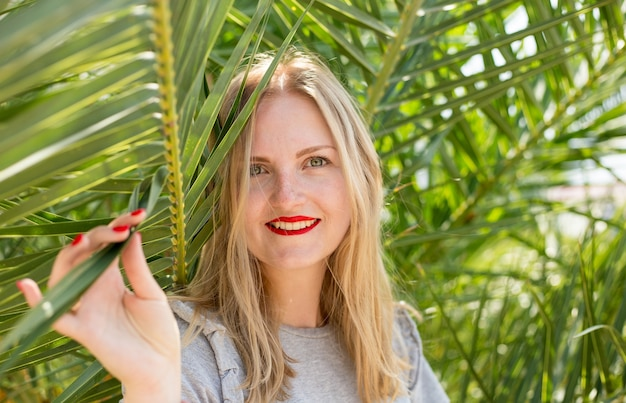 Beautiful girl with red lips smiling and posing in tropical forest. portrait of tender woman looking out of palm leaf