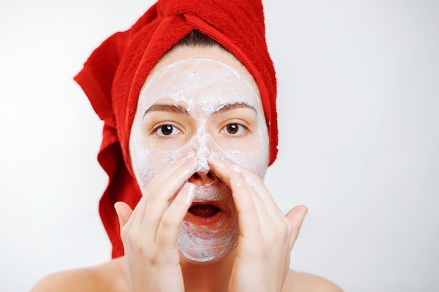 Beautiful girl with a red towel on her head puts a scrub on her nose