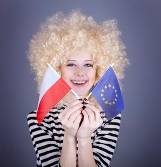 リングレットを持つ美しい少女は、欧州連合とポーランドの旗を示しています。