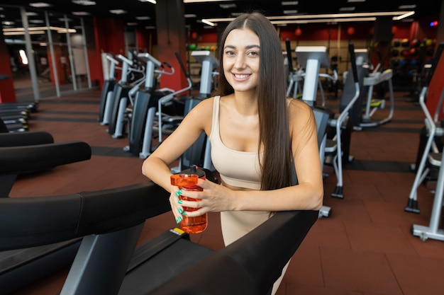 Beautiful girl with a shaker in hand on a treadmill