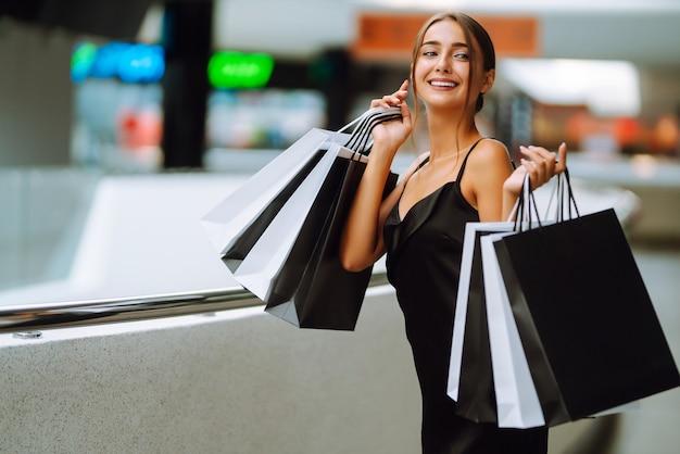 Красивая девушка с хозяйственными сумками смотрит в камеру и улыбается, делая покупки в торговом центре