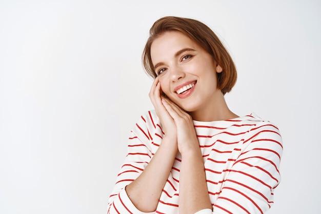 짧은 머리와 자연스러운 화장을 한 아름다운 소녀, 귀여운 것에 감탄하고, 애정에 감동하고, 웃고, 흰 벽에 기대어 서 있습니다.