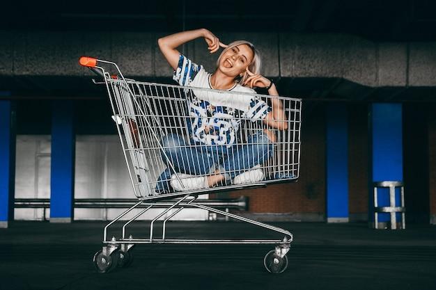 쇼핑을 하고 청바지를 입은 짧은 흰 머리를 가진 아름다운 소녀가 주차장에서 카트에 올라탔다