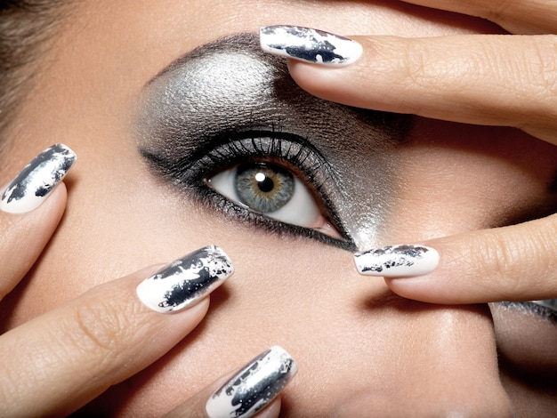 Beautiful girl with the silver  makeup of eyes and  metal nails.