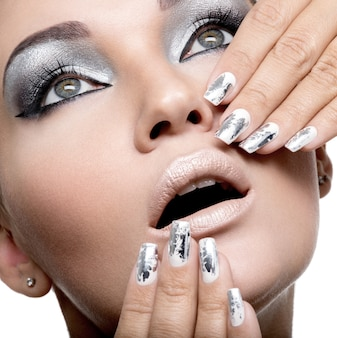 Beautiful girl with the silver makeup and  metal nails.
