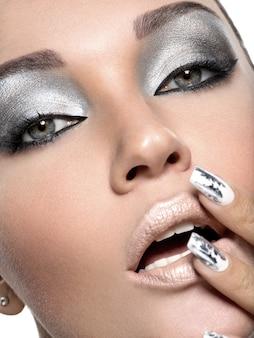 Bella ragazza con il trucco d'argento e chiodi di metallo.