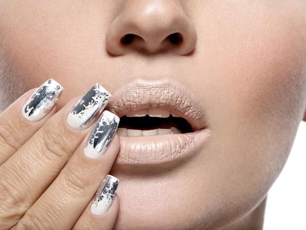 Bella ragazza con i chiodi in metallo argentato.
