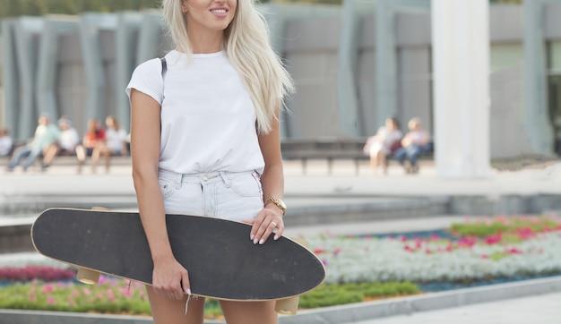 スケートボードで美しい少女。スケートボードを手で押しの女の子。ジーンズのショートパンツの女の子の手でロングボード。手にロングボードを持つ公園の少女