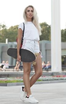 スケートボードで美しい少女。スケートボードを手で押しの女の子。