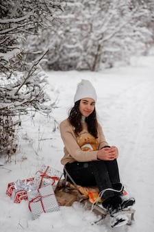 Красивая девушка с елкой санки и подарками зимой в заснеженном лесу