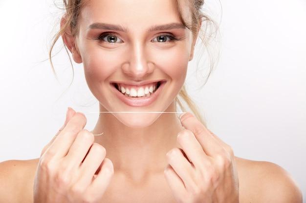 白いスタジオの背景に真っ白な歯を持つ美しい少女、歯科のコンセプト、完璧な笑顔、カメラを見て、クローズアップ、デンタルフロスを使用して笑顔。