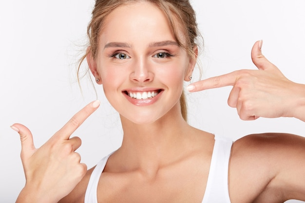 Красивая девушка с белоснежными зубами на белом фоне студии, концепции стоматологии, идеальной улыбкой, указывая на зубы.
