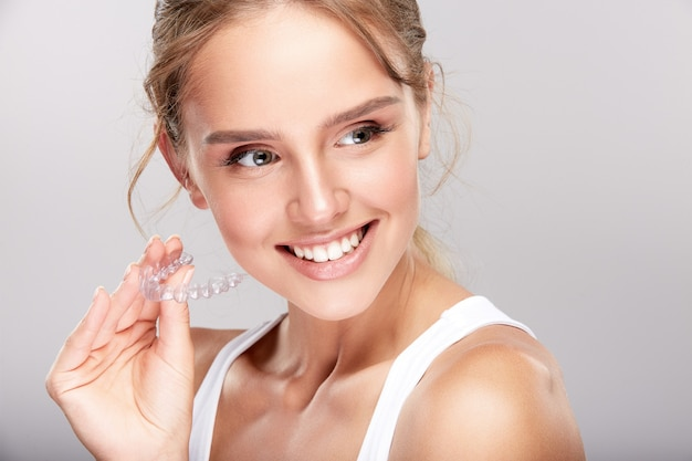 Beautiful girl with snow white teeth on white studio background, dentistry concept, perfect smile, looking at camera, close up, holding dentifrice.