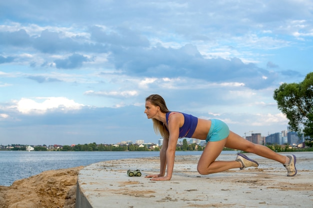 The beautiful girl with a sports figure does fitness outdoors near the lake.