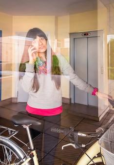 유리벽 뒤 건물 홀에서 운동복과 픽시 바이크를 입은 아름다운 소녀