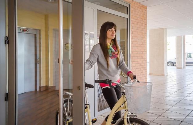 유리문을 여는 건물 홀에서 운동복과 픽시 자전거를 입은 아름다운 소녀