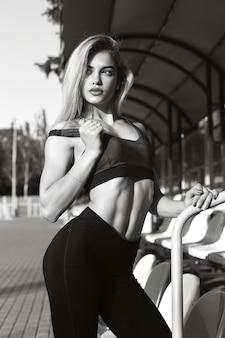 Beautiful girl with a sporty body posing at the stadium