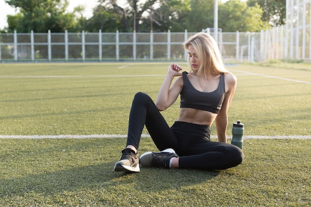Beautiful girl with a sporty body sits on the grass at the stadium