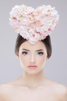 Красивая девушка с весенним сердцем из цветов на голове и креативным макияжем
