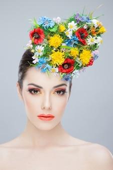 Красивая девушка с весенними яркими цветами и голыми плечами