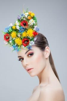 Красивая девушка с весенними яркими цветами на голове