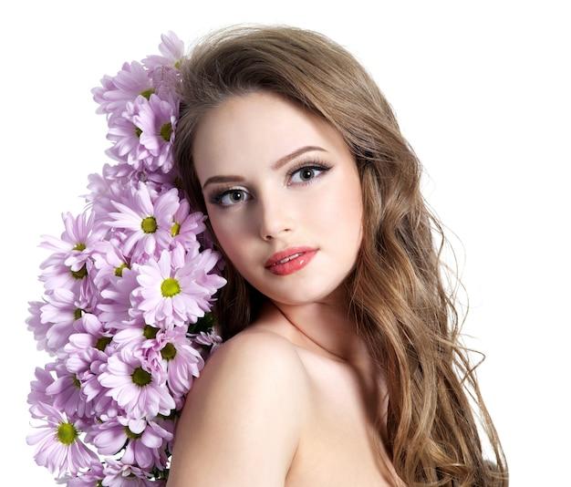 春の花を持つ美しい少女-白い背景で隔離