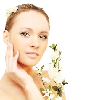 白で隔離春の花を持つ美しい少女
