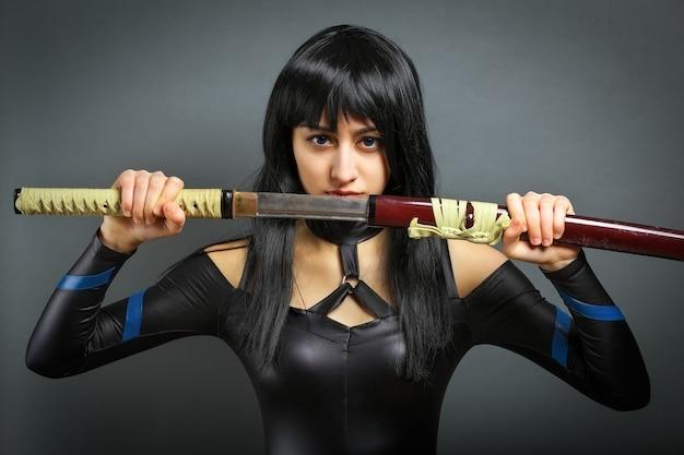 Красивая девушка с мечом на сером фоне. она вытаскивает меч