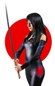 Красивая девушка с мечом на фоне японского флага. девушка позирует с мечом
