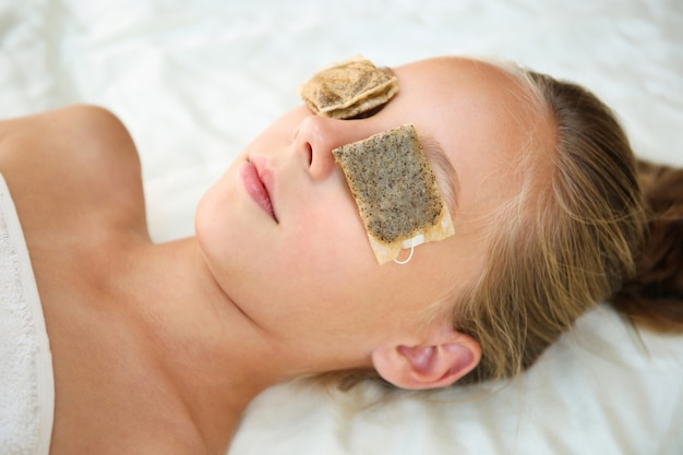 Beautiful girl with tea bags on eyes. top view.