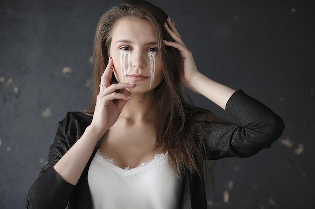 눈에 눈물을 가진 아름 다운 소녀입니다. 카메라에 포즈 그린된 눈물 어린 소녀입니다. 마스크와 메이크업 카니발 소녀입니다.