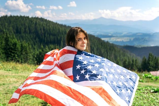 Красивая девушка с американским флагом в горной долине 4 июля четвертое июля свободы