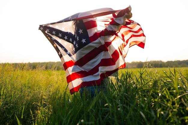 Красивая девушка с американским флагом в пшеничном поле 4 июля в день независимости