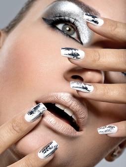 銀の化粧と金属の釘を持つ美しい少女。ファッションの女性の肖像画。