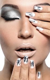 Красивая девушка с серебряным макияжем и металлическими гвоздями.