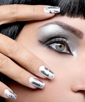 目と金属の釘の銀の化粧を持つ美しい少女。