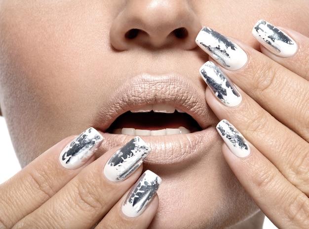 銀の金属の釘を持つ美しい少女。