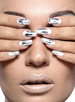 은색 금속 손톱을 가진 아름 다운 소녀입니다.