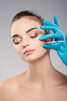Beautiful girl with thick eyebrows at studio background, doctor's hands wearing blue gloves near patient's face, holding syringe near face.