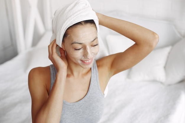 Beautiful girl with a towel using a beauty product