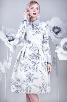 暖かい冬のウールのドレスでヴィンテージメイクと髪型の美しい少女。花の装飾。顔の美しさ。スタジオで撮影した写真