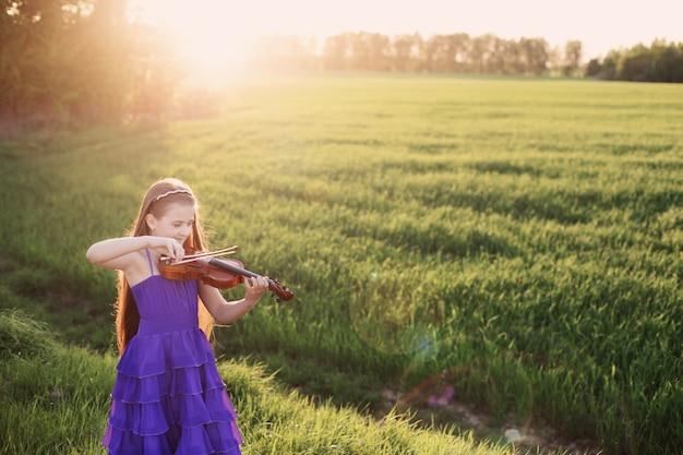 Красивая девушка со скрипкой на открытом воздухе