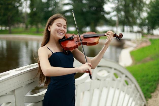 Красивая девушка со скрипкой, улыбаясь в природе. фото высокого качества