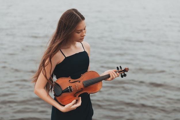 A beautiful girl with a violin stands against the background of water. asian appearance. musical concept. high quality photo