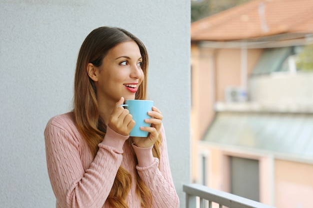 朝は温かい飲み物を楽しむ暖かいセーターで美しい少女